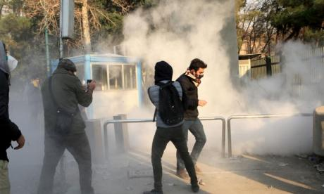 Students are seen running for cover from tear gas at the University of Tehran as protests continue across Iran