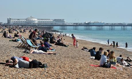 People enjoying the sunny weather conditions as they sit on Brighton beach