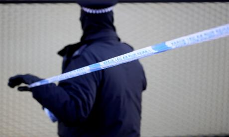 A police officer marks a corden near the scene where a man, aged 18, was fatally stabbed on Wednesday